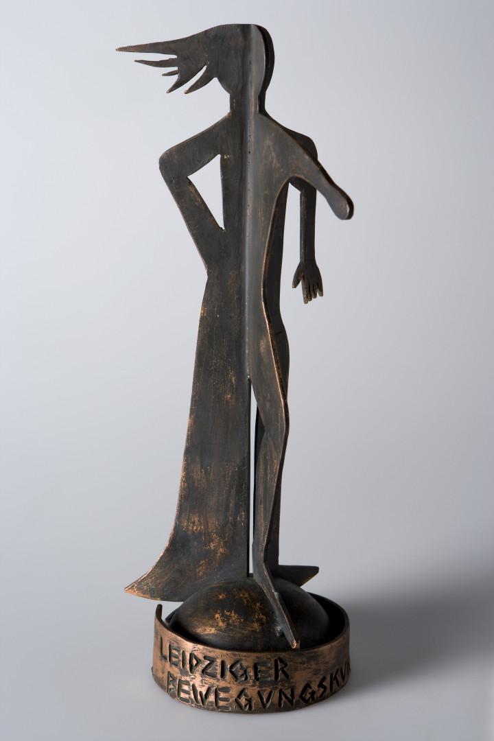 In seiner Formensprache verkörpert der Figurenentwurf von Alexander Amm alles, was die Initiatoren des Bewegungskunstpreises inhaltlich mit der Auszeichnung würdigen möchten: Die Beharrlichkeit aller freien Tanz-, Theater und Performance-Künstler und deren Mut, künstlerische Arbeiten, die ohne oder mit sehr geringer Förderung auskommen müssen, trotzdem einem Publikum zu präsentieren. Sie bilden einen Bereich der Kunst, in dessen Mittelpunkt der Mensch, seine Bewegungen und seine Fähigkeit zum szenischen Verarbeiten stehen. Von Kunstschmied Theo Braun geformt und ins Leben geholt, verdichtet die Preisfigur diese Aussage in einer hochwertigen und ästhetisch anspruchsvollen Arbeit.